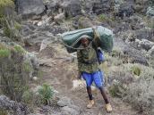 Фото из тура в Танзанию в 2005 году. Портер с баулом на тропе.