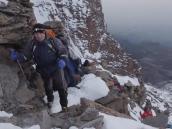 Ступень за ступенью, на фоне 500-метровой вертикальной стены пика Ухуру.