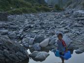 Мальчик с лейками у речной лужи